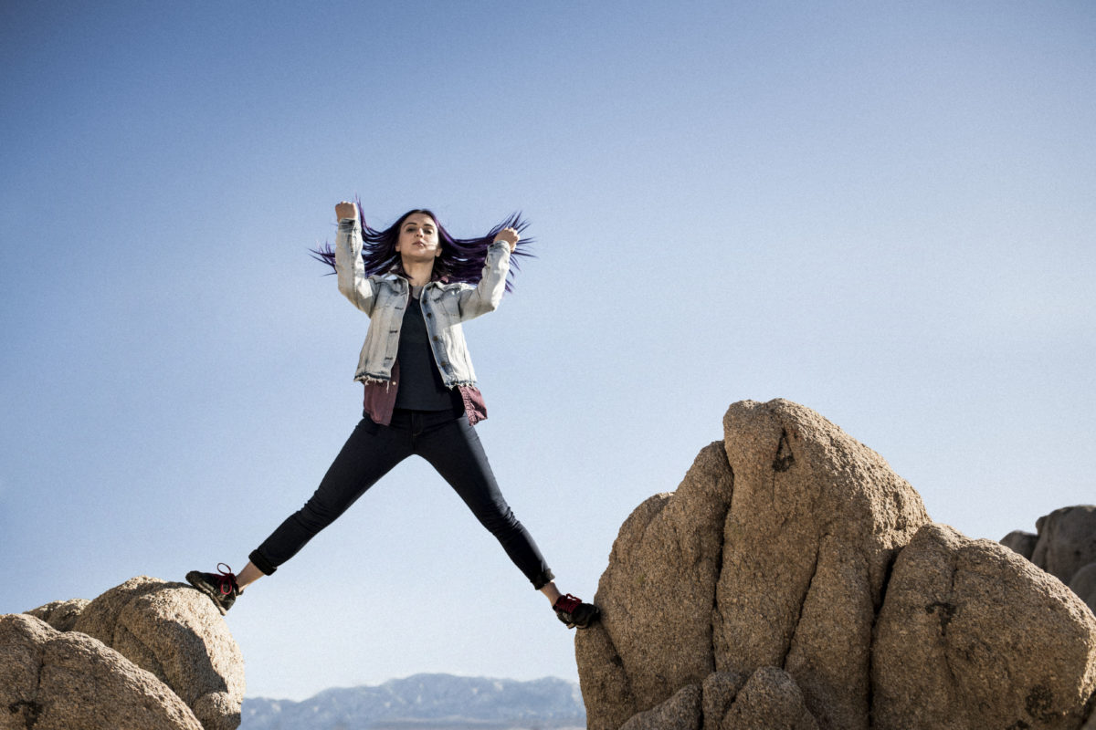 A woman standing atop large rocks — part of a campaign supporting REI's brand positioning strategy