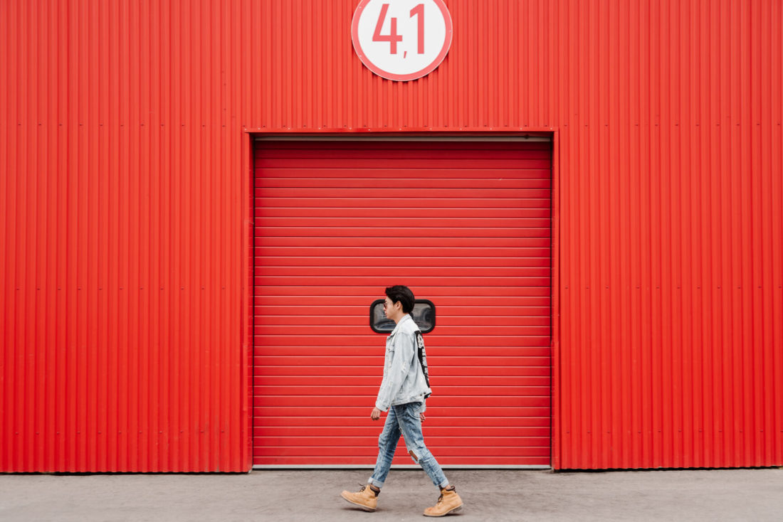 A man walking in front of a red wall